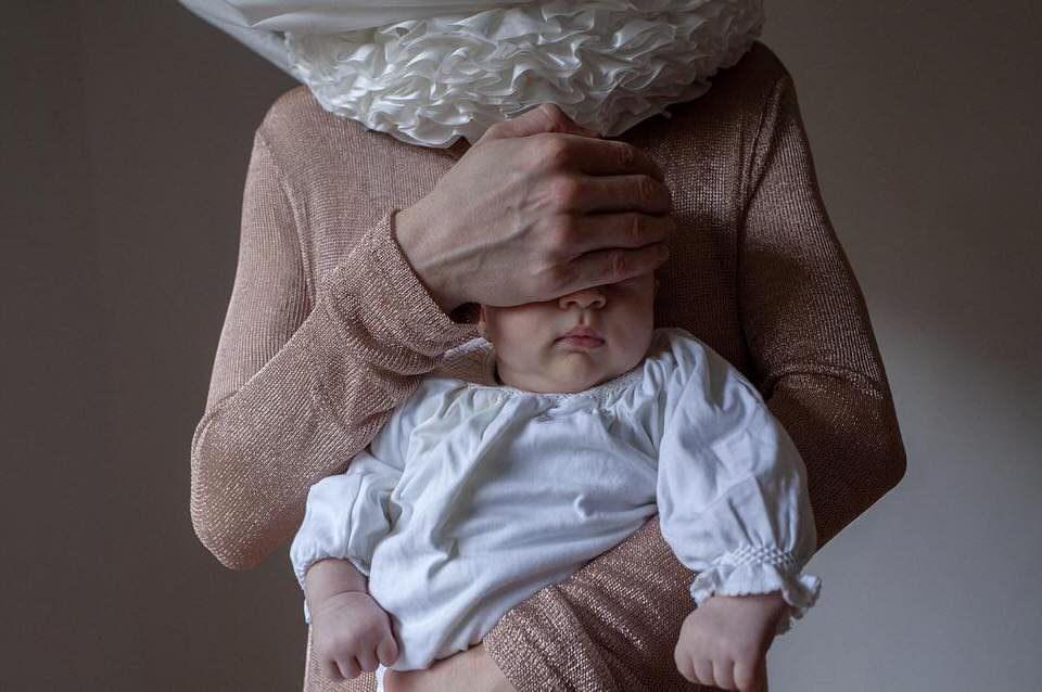 Mensch hält einem Baby die Augen zu