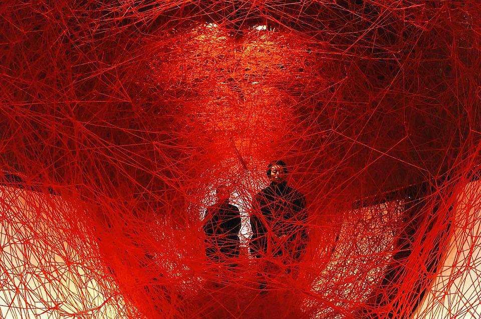 Zwei Personen hinter roten Fäden
