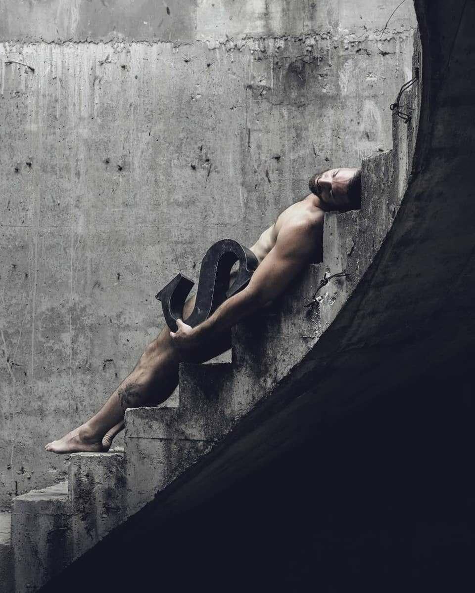 Nackter Mann liegt auf einer Steintreppe mit einem S