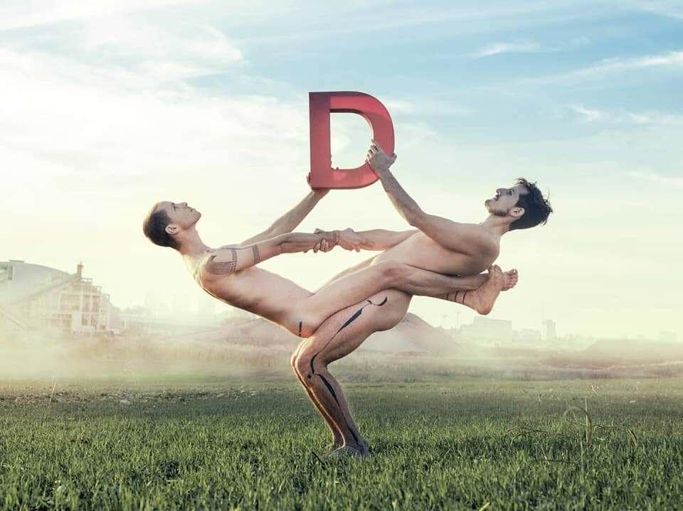 Zwei nackte Männer in akrobatischer Pose mit einem D