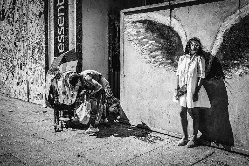 Frau mit gemalten Flügeln und Obdachlose