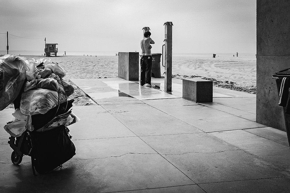 Ein Mann duscht am Strand, im Vordergrund Müll