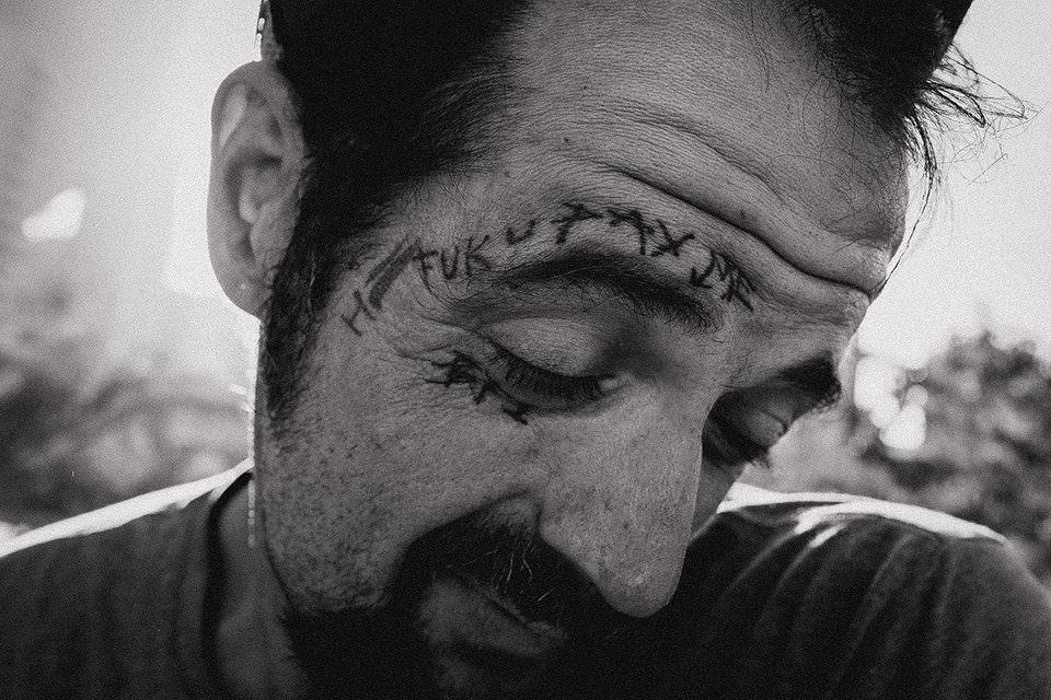 Mann mit Tattoo über dem Auge