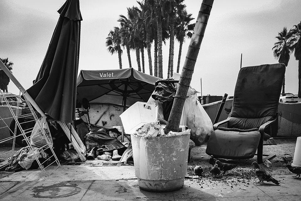 Zeltende Menschen zwischen Müll