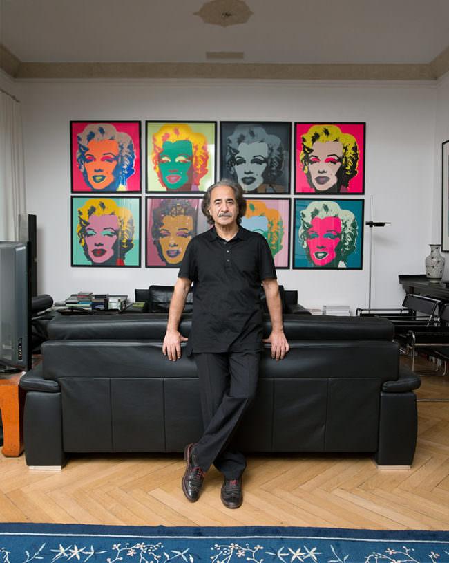Man vor Warhol-Bildern, an einem Sofa lehnend.