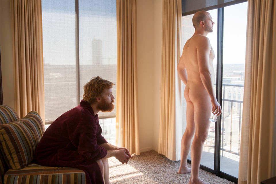 Ein Mann sitzt auf einem Sessel, ein anderer steht nackt am Fenster