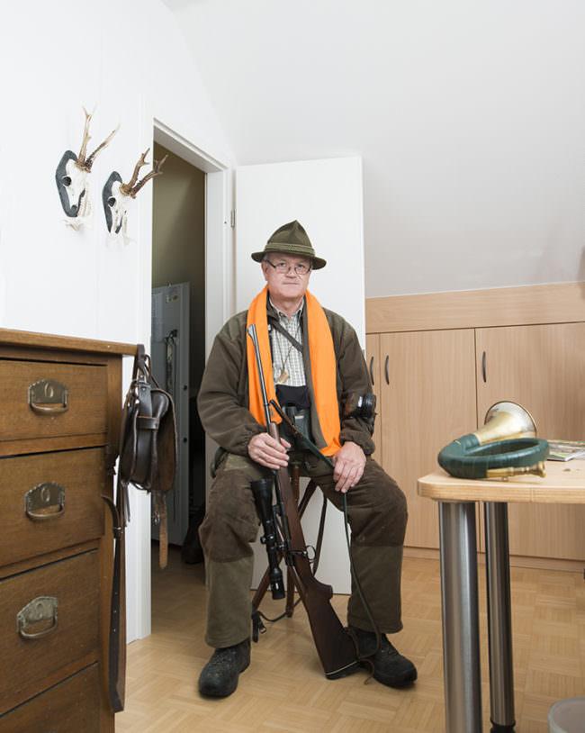 Mann in Jagdkluft mit Gewehr