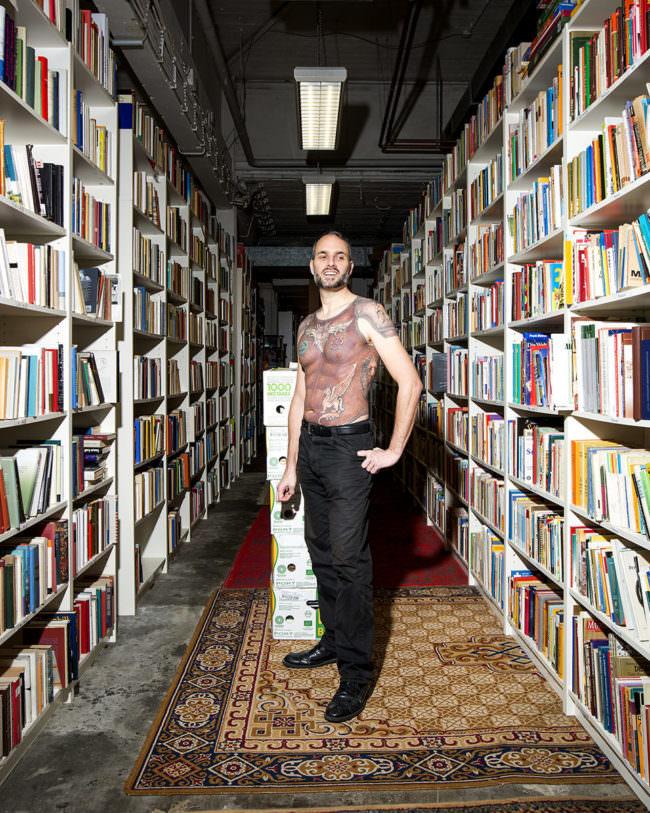 Mann zwischen zwei Bücherwänden