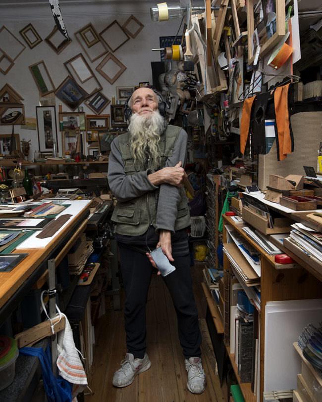 Älterer Mann in Werkraum mit Handy in der Hand