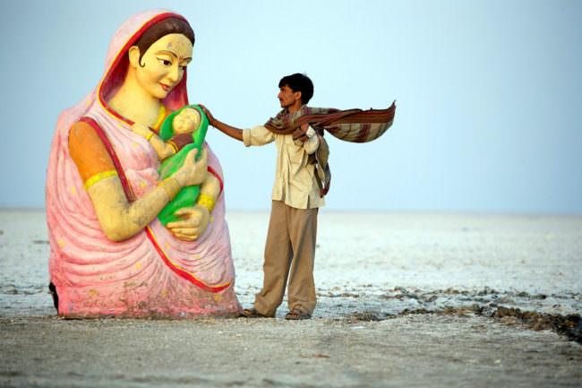 Mann berührt bunte Statue