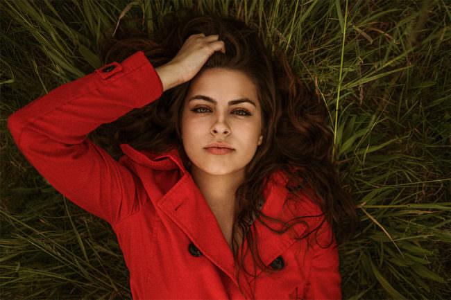 Frau liegt im Gras