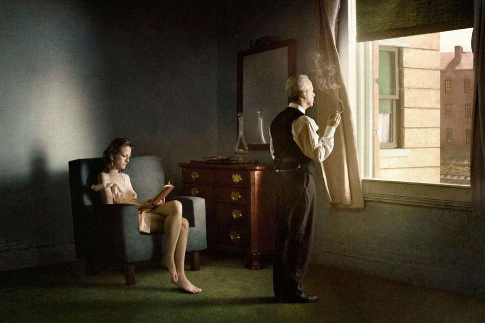 Frau auf einem Sessel und Mann sieht aus dem Fenster