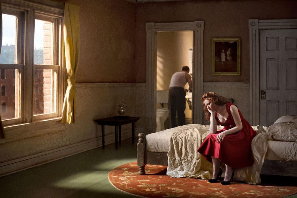Frau sitzt auf einem Bett, im Hintergrund ein Mann im Bad