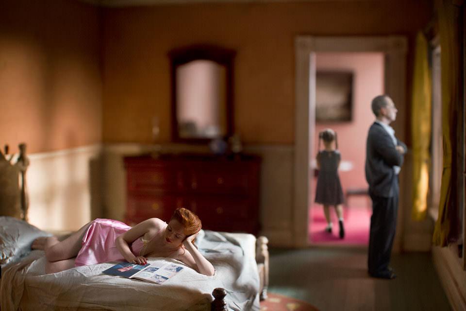 Frau liest auf einem Bett, Im Hintergrund die Familie
