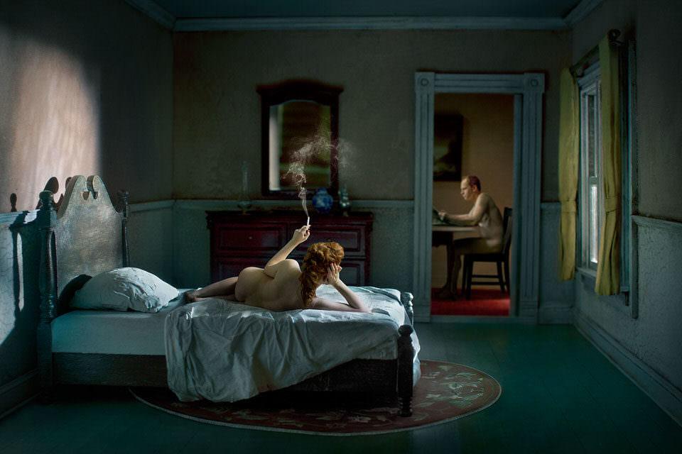 Rauchende Frau liegt auf dem Bett und sieht zu einem Mann im anderen Zimmer