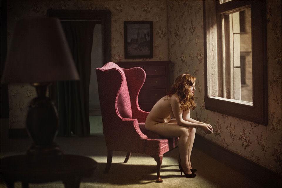 Nackte Frau auf einem Stuhl sieht aus dem Fenster