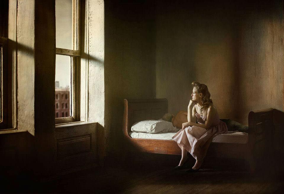 Frau sitzt auf dem Bett und sieht aus dem Fenster