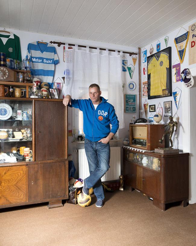 Mann in Trikot mit Fußballdingen umgeben