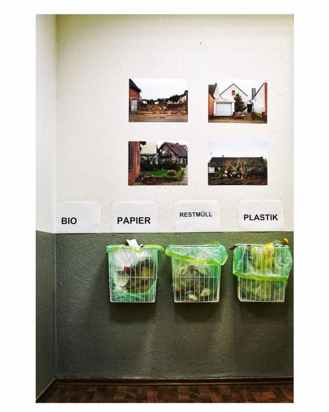Müllbehälter unter ausgestellten Bildern
