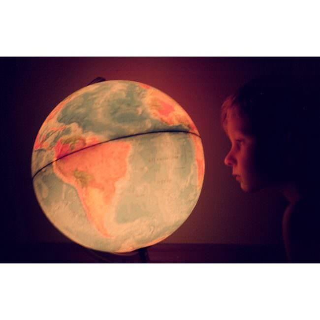 Ein Junge sieht einen Globus an
