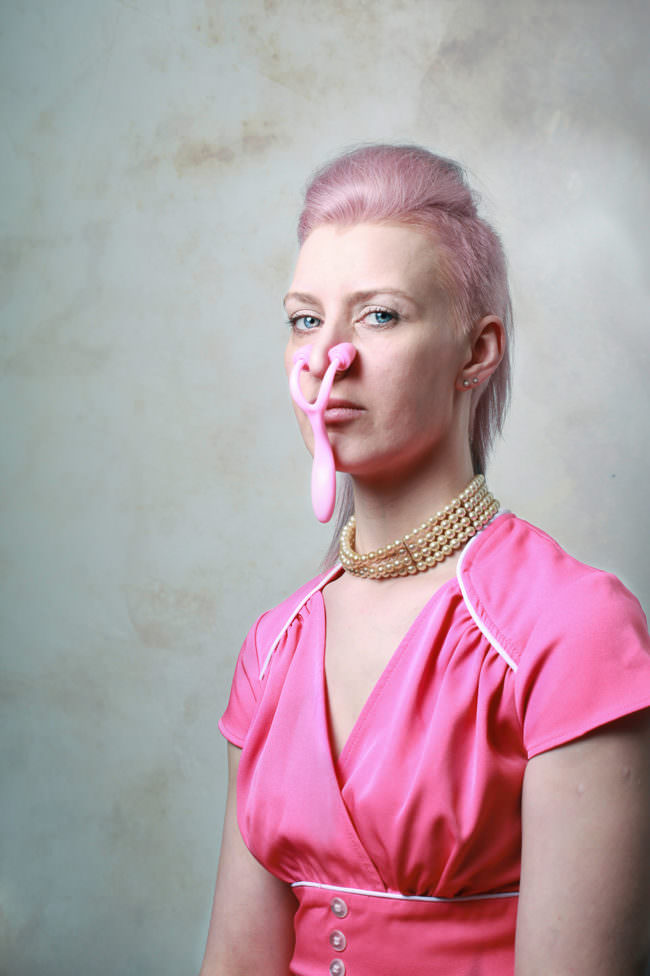 Frau mit rosa Plastikgerät an der Nase