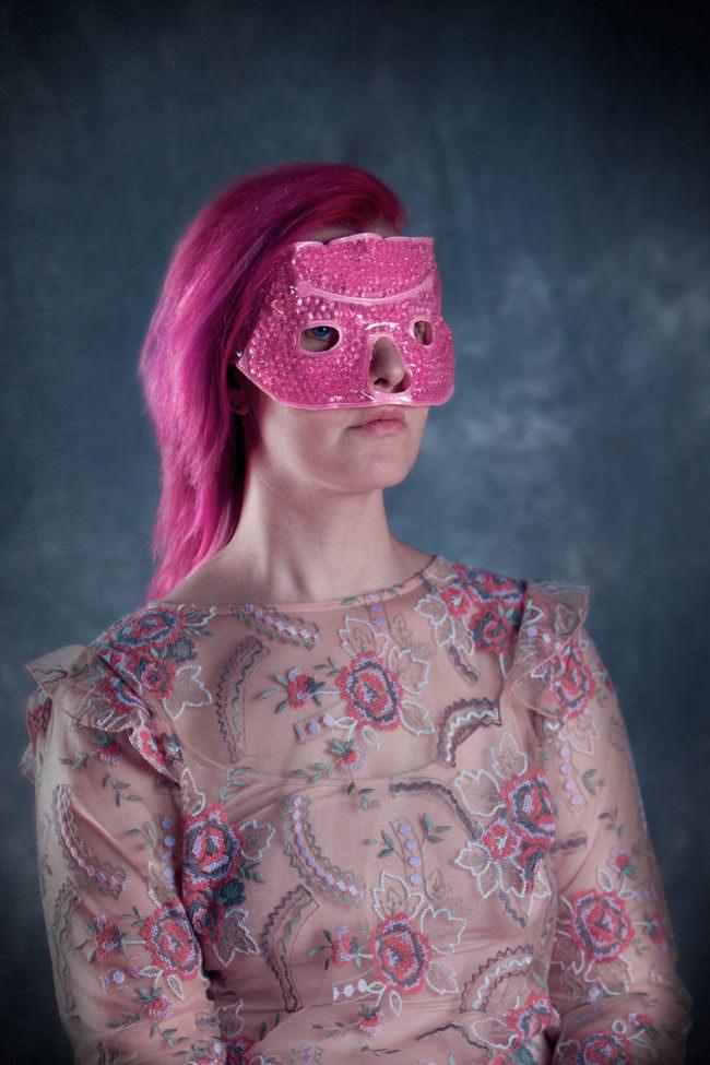 Frau mit rosaner Maske