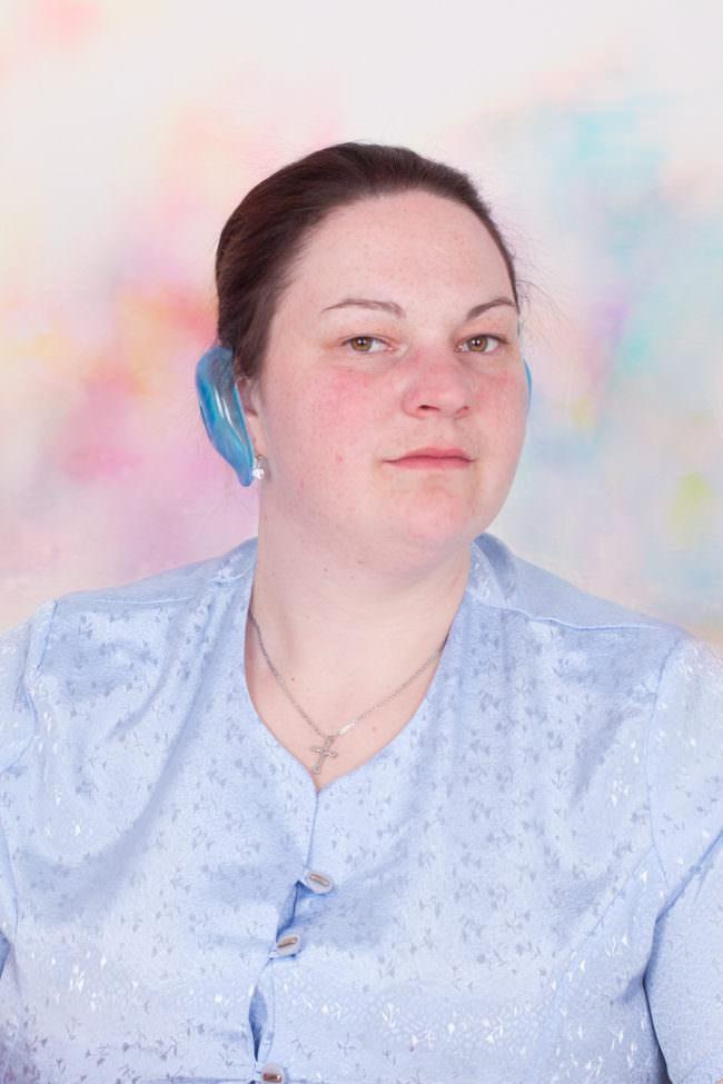 Frau mit blauer Plastik am Ohr