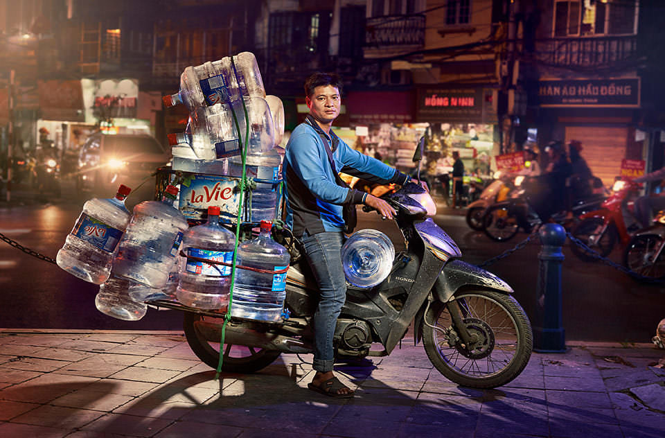 Mann transportiert Wasserflaschen auf einem Motorrad