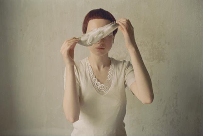 Eine Frau hält einen Flügel vor ihren Augen.
