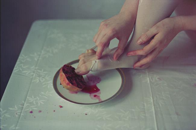 Fuß in Strumpfhose, Hand, Granatapfel auf einem Teller auf einem Tisch