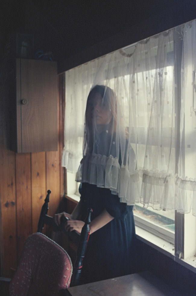 Eine Frau versteckt sich hinter einer Gardine