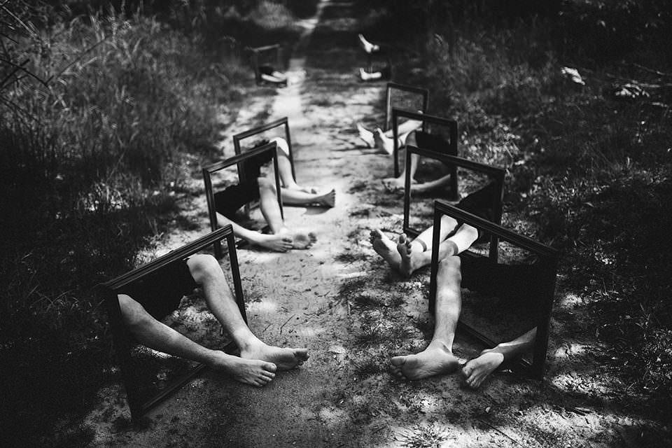 Viele Beine ragen aus Bilderrahmen am Rand eines Feldwegs.