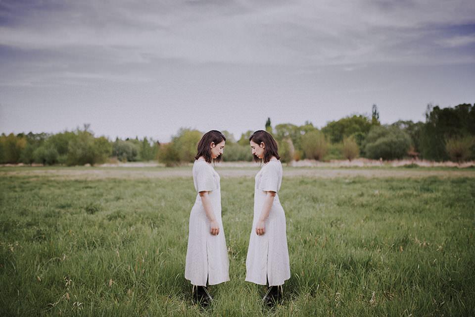 Zwillinge einander zugewandt auf einem Feld