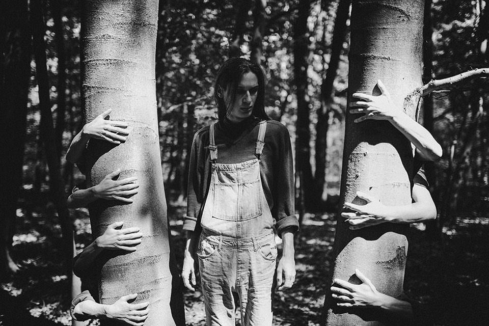 Frau mit vielen Händen um einen Baum