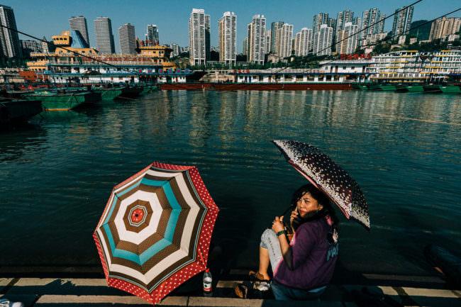 Zwei Menschen mit Regenschirmen an einem Fluss. Im Hintergrund deine Großstadt