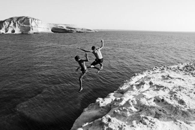 Kinder springen von einer Klippe ins Wasser