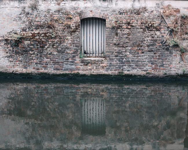 Fenster mit Gittern spiegelt sich im Wasser