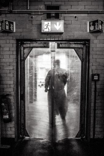 Mann hinter einer durchsichtigen Tür