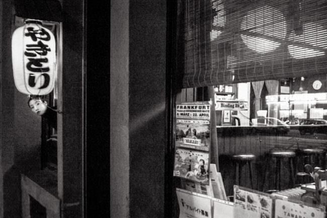 Frau sieht aus dem Fenster eines Ladens