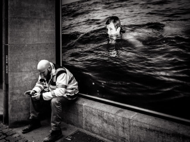 Mann sitzt vor einem Plakat mit Schwimmerin