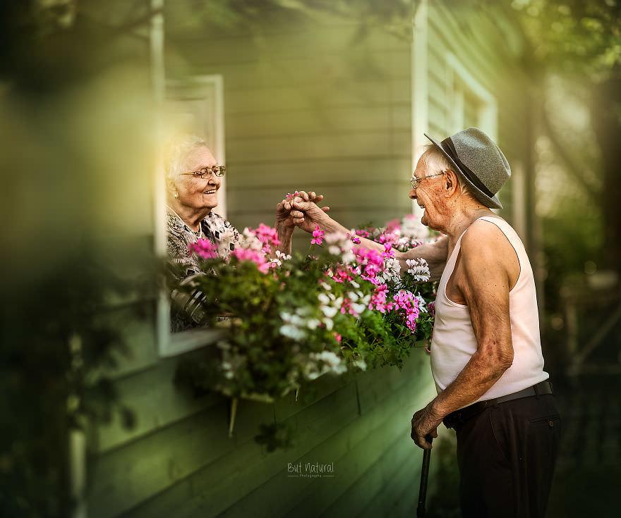 Mann begrüßt Frau über den Balkon