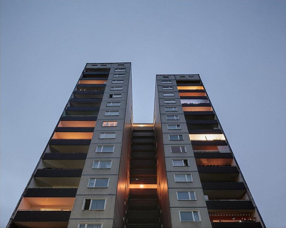 Plattenbau mit unterschiedlich beleuchteten Balkonen vor blauem Himmel