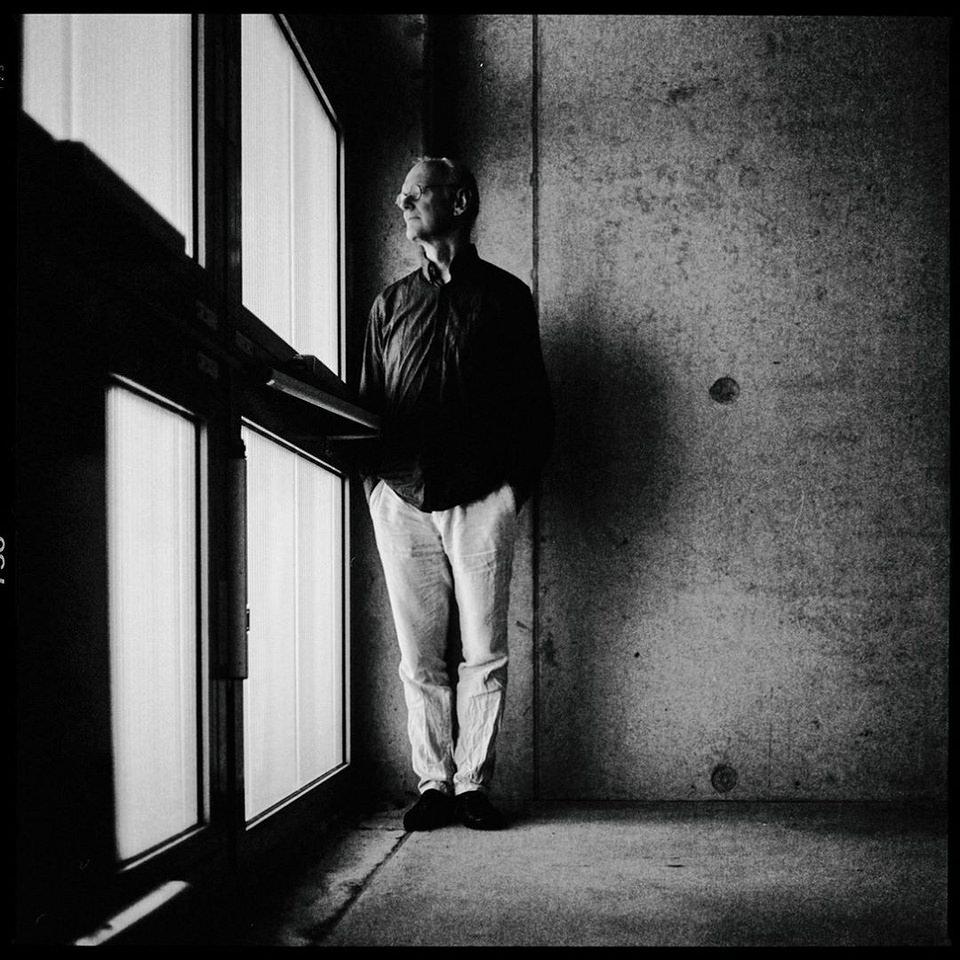 Portrait eines Mannes, an einer Fensterfront stehend