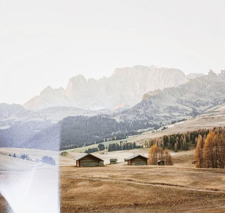 Berglandschaft mit Feldern, Wald und Hütten