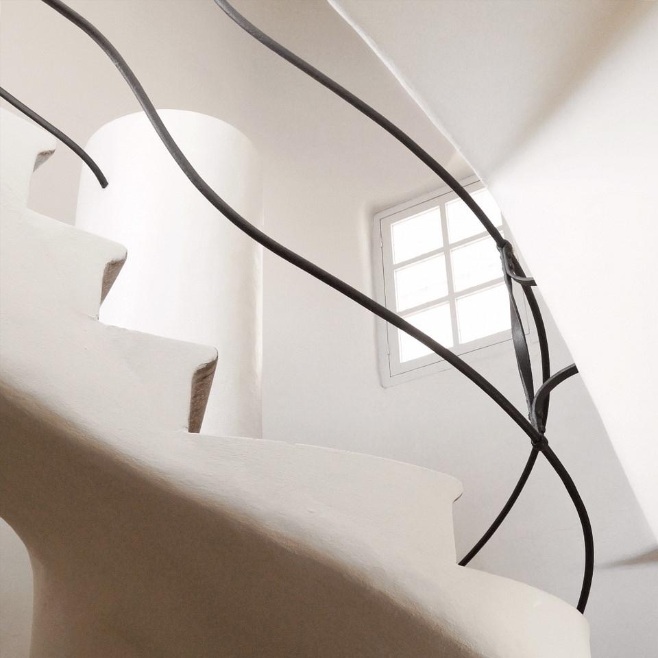 schwarzes, schmiedeeisernes Geländer in einem weißen Treppenhaus