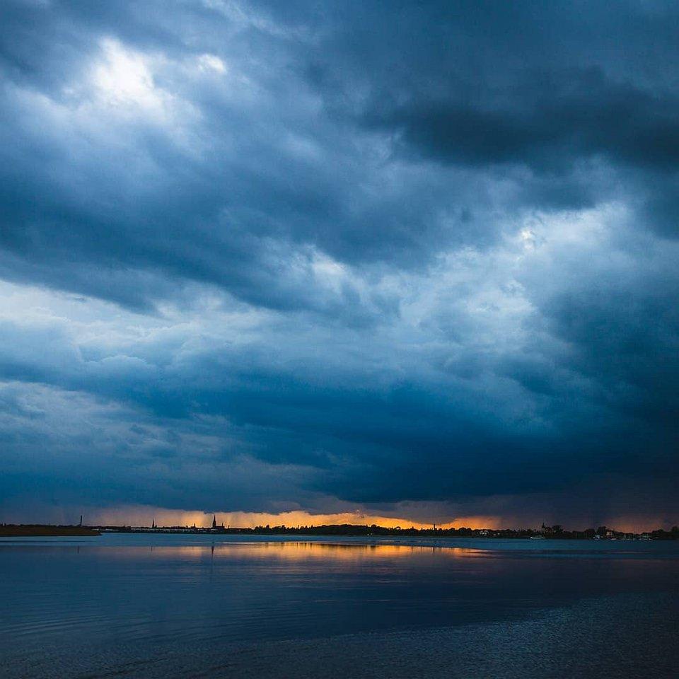 goldener Streifen am Horizont hinter dunkelblauer Wolkenfront über einer Stadt am Fluss