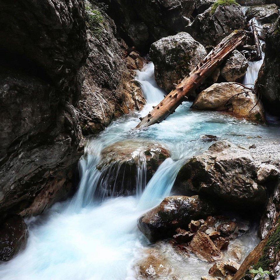 Wasserlauf zwischen Felsen mit Baumstämmen