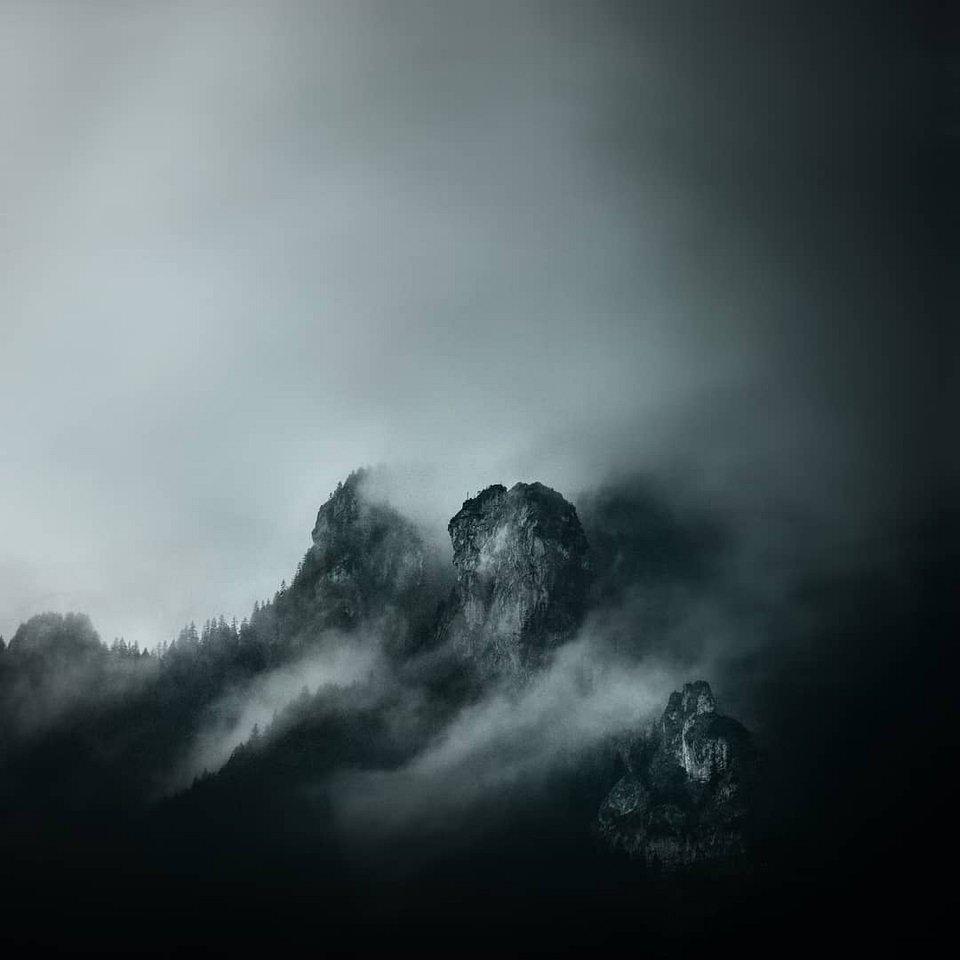 tiefhängende Wolken über bewaldeten Berggipfeln in Dunkelheit