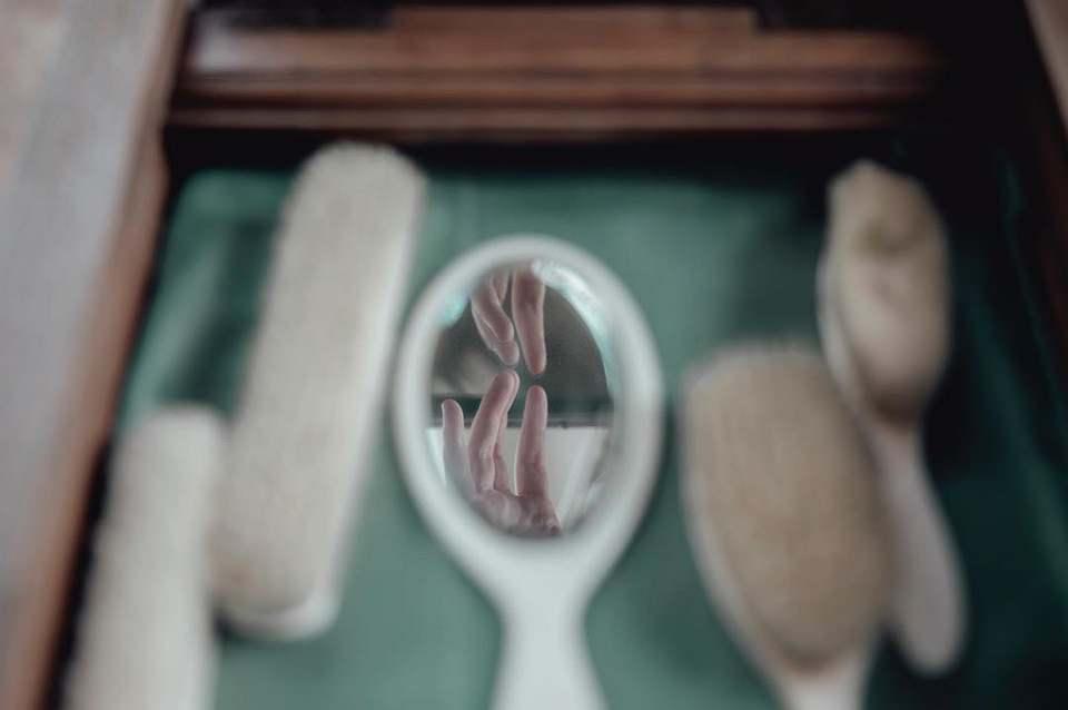 Spiegelung einer Hand in einem Handspiegel neben Bürsten