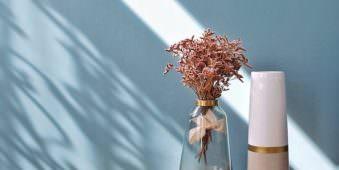 zwei Vasen und ein Blumenstrauß auf einem Tisch vor blauer Wand mit Lichtstreifen und Schatten